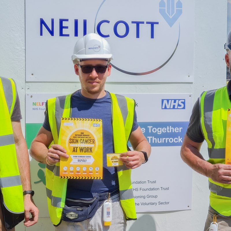Three construction workers holding posters for new skin cancer campaign